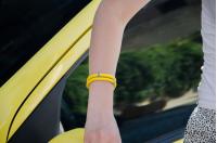 Браслет на желтом шнуре с символами на руке